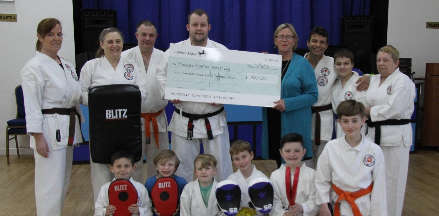 members of Horden Martial Arts Club Chris Anderson holding the cheque with Cllr June Clark.
